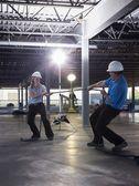 Ingenjörer leka dragkamp på byggarbetsplats — Stockfoto