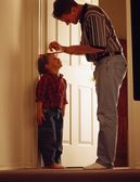 Father Measuring Son On Door Frame — Stock Photo