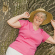 Senior Woman Leaning Against A Tree — Stock Photo