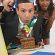Businessman Blowing Out Candle On Birthday Cake — Stock Photo