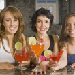 Three Girl Friends Standing At A Table Drinking Cocktails — Stock Photo