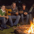 Four Teenage Boys Sitting By Campfire — Stock Photo