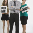 Two Women Holding Signs Beside A Businessman — Stock Photo