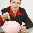 Stock Photo: BusinesswomPutting Penny In Piggy Bank