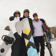 Three Adults At A Ski Resort, Holding Snowboards And Skis — Stock Photo #31935989
