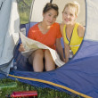 Two Girl Friends Sitting In A Tent Reading A Map — Stock Photo