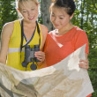 Two Girl Friends In A Forest Holding Binoculars And A Map — Stock Photo