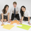 Stock Photo: Three People Sitting On Floor Looking At Puzzle Pieces