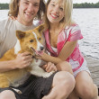 Couple Sitting On A Shoreline With Their Dog — Stock Photo