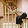 Girl goes down the banisters — Stock Photo