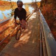 Cyclist On Wooden Pathway By River — Stock Photo