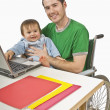 Man In A Wheelchair Holding His Son While Working On Laptop — Stock Photo