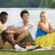Three Friends Having A Picnic By The Water — Stock Photo #31937901