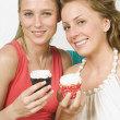 Stock Photo: Two Women Holding Cupcakes