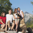 Family Sitting On The Rocks In The Mountains With Their Dog — Foto de Stock
