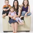 Mother And Her Children Sitting Together In Living Room Chair — Stock Photo