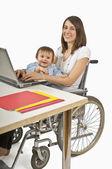 мать в инвалидной коляске baby холдинг пока печатающ на машинке на ноутбуке — Стоковое фото