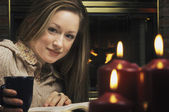 Young Woman Reading Book In Front Of Fireplace — Stock Photo