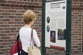 Woman Reading Park Information Sign — Stock Photo
