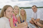 Four People On A Dock Surrounded By Water — Stock Photo
