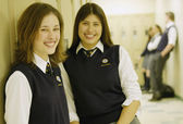 Female Students Standing In Hallway — Stock Photo