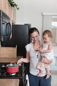 Mother Cooking And Holding A Baby — Stock Photo