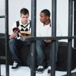 Young Man Reading The Bible To Another Young Man In Jail — Stock Photo