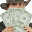 Stock Photo: WomPeeking From Behind Oversized Dollar Bills