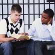 Young Man Reading The Bible To Another Young Man In Jail — Foto Stock