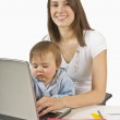 Mother Sitting With Toddler On Her Lap While Typing — Stock Photo