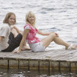Two People Sitting On A Dock And Surrounded By Water — Stock Photo