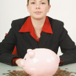 Stock Photo: BusinesswomSitting At Desk With Piggy Bank