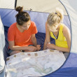 Two Girl Friends Sitting In A Tent Reading A Map — Foto Stock