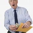 Stock Photo: Surprised Businessman Putting Money In An Envelope