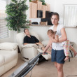 Mother Trying To Vacuum While The Father Sits Around — Stockfoto