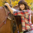 Stock Photo: WomPutting Saddle On Horse