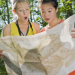 Two Girl Friends In The Forest Looking At A Map — Stock Photo