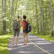 Two Girl Friends Looking Into The Forest From A Bike Path — Stock Photo
