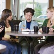 Group Of Girls Listening To Senior Woman In Restaurant — Stock Photo