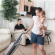 Mother Trying To Vacuum While The Father Sits Around — Foto de Stock