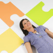 Stock Photo: WomLying On Floor Beside Oversized Puzzle Pieces