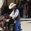 Stock Photo: Cowboy Working On Saddle