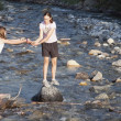 Two Girls Playing On The Rocks In The River — Stock Photo
