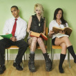 Stock Photo: Three People Sitting In Row On School Chairs
