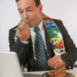Stock Photo: BusinessmEating Birthday Cake At His Desk