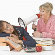 Stock Photo: Teacher Holding Megaphone Beside Sleeping Student