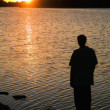 Silhouette Of A Man Standing On The Shore Watching The Sunset — Stock Photo