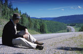 Hiker Sitting On Edge Of Country Road — Stockfoto