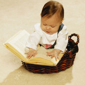 Baby Reading A Book In A Basket — Stock Photo