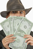 Woman Peeking From Behind Oversized Dollar Bills — Foto Stock